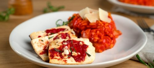 Risotto with tomato and tofu on a plate.