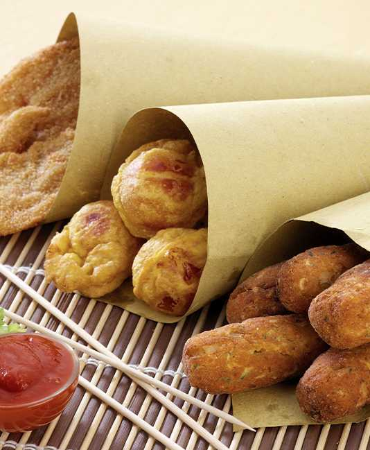 Vegetable fritters rolled in paper with ketchup.