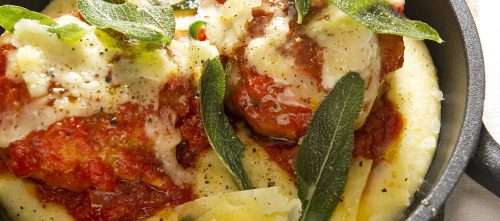 Veal meatballs in tomato sauce served with polenta and sage