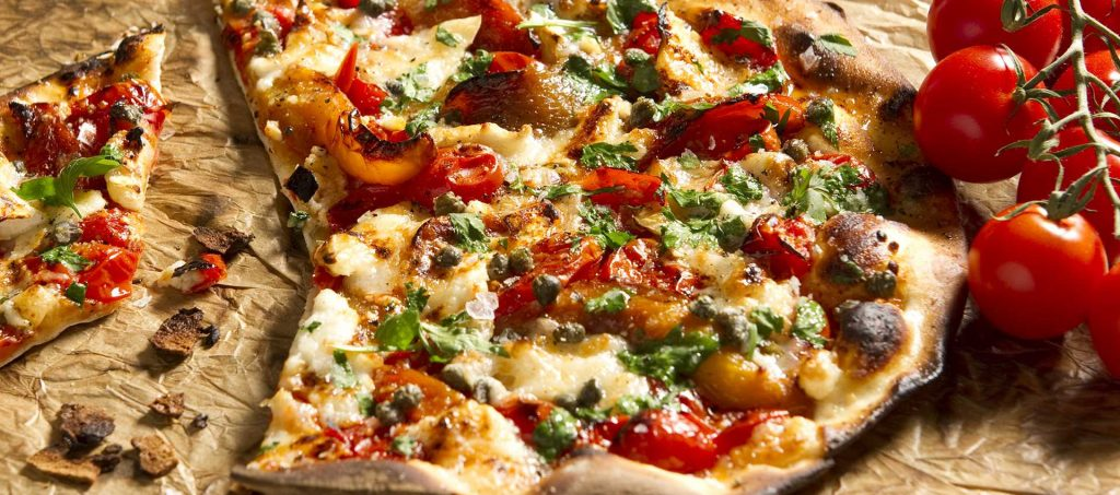 Pizza with tomatoes, goat cheese, bell peppers, capers and herbs