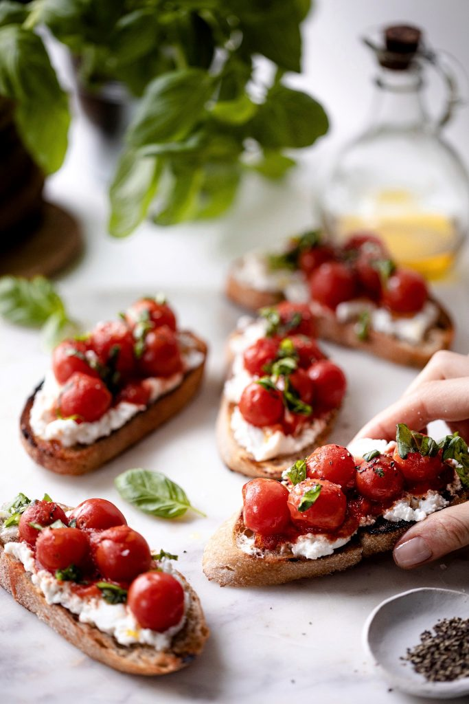 Grilled Crostini with warm cherry tomato topping and fresh basil