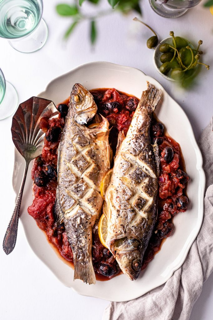 Baked Whole Sea Bass with black olives, tomato and capers sauce